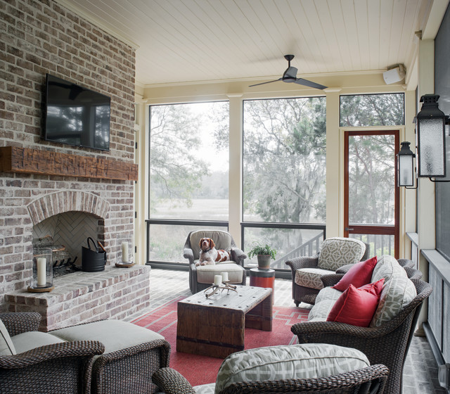 This is an example of a country brick screened-in porch design in Atlanta with a roof extension.