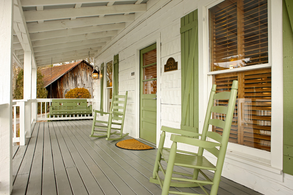This is an example of a rustic front porch design in Other with decking and a roof extension.