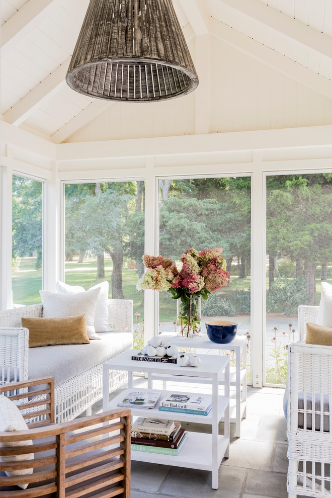 Beach style stone screened-in side porch idea in Boston with a roof extension