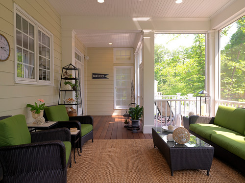 A stylish porch featuring rustic wicker chairs, green cushions, and a wooden coffetable