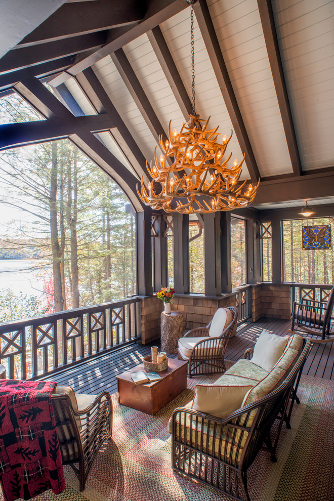 Large mountain style screened-in porch photo in New York with decking and a roof extension