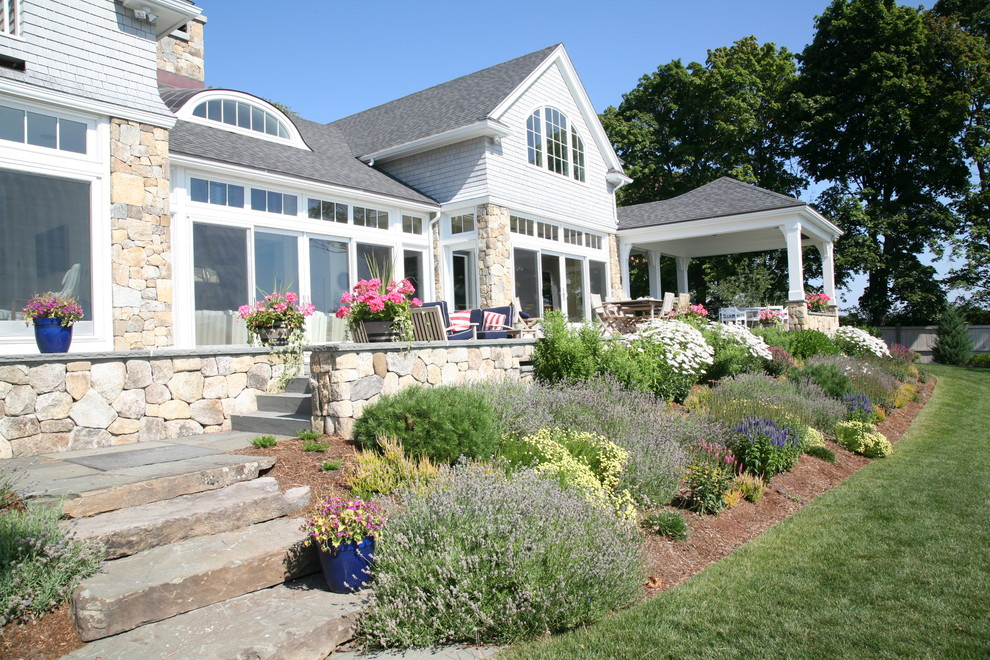 This is an example of a large craftsman stone back porch design in Boston.