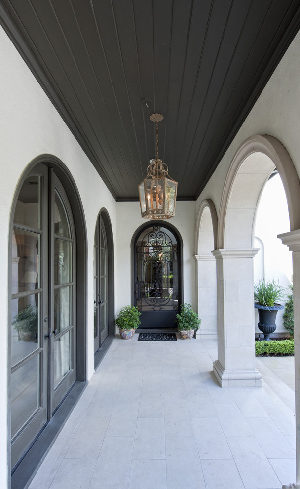Tuscan porch photo in Houston with a roof extension