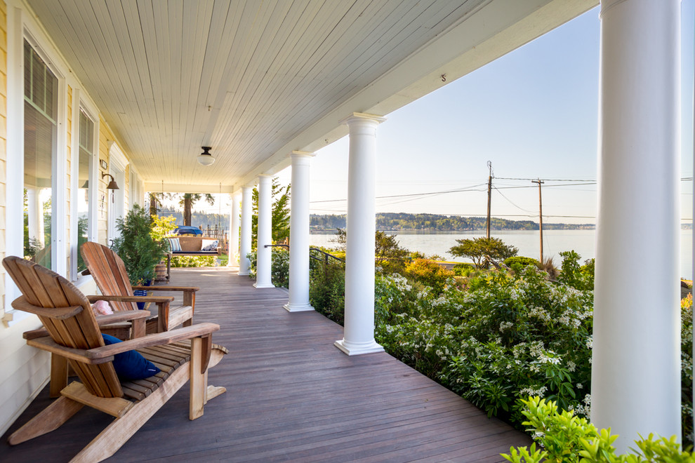 This is an example of a large cottage front porch design in Seattle with decking and a roof extension.