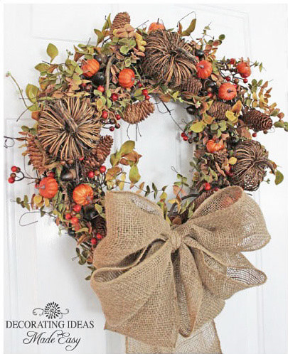 a bucolic wreath featuring pine cones, twigs and pumpkins