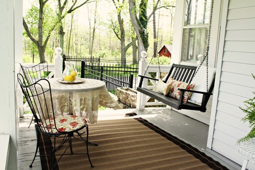Porch with steel chair, steel porch table, and wooden swing with throw pillows