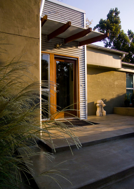 Inspiration for a mid-sized contemporary concrete front porch remodel in Other with an awning
