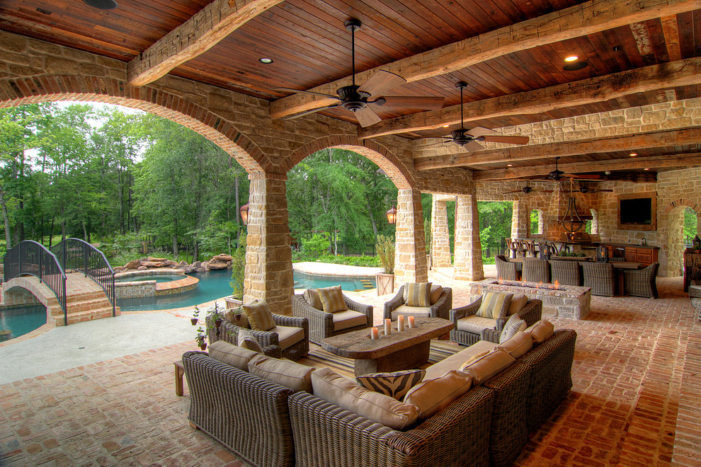 Inspiration for a mediterranean brick porch remodel in Houston with a fire pit and a roof extension
