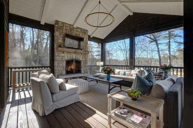 This is an example of a transitional screened-in porch design in Other with decking and a roof extension.