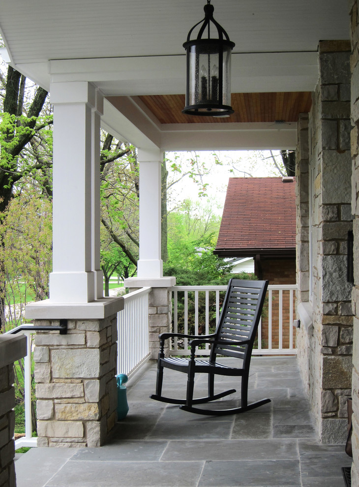 Inspiration for a large country stone front porch remodel in Chicago with a roof extension
