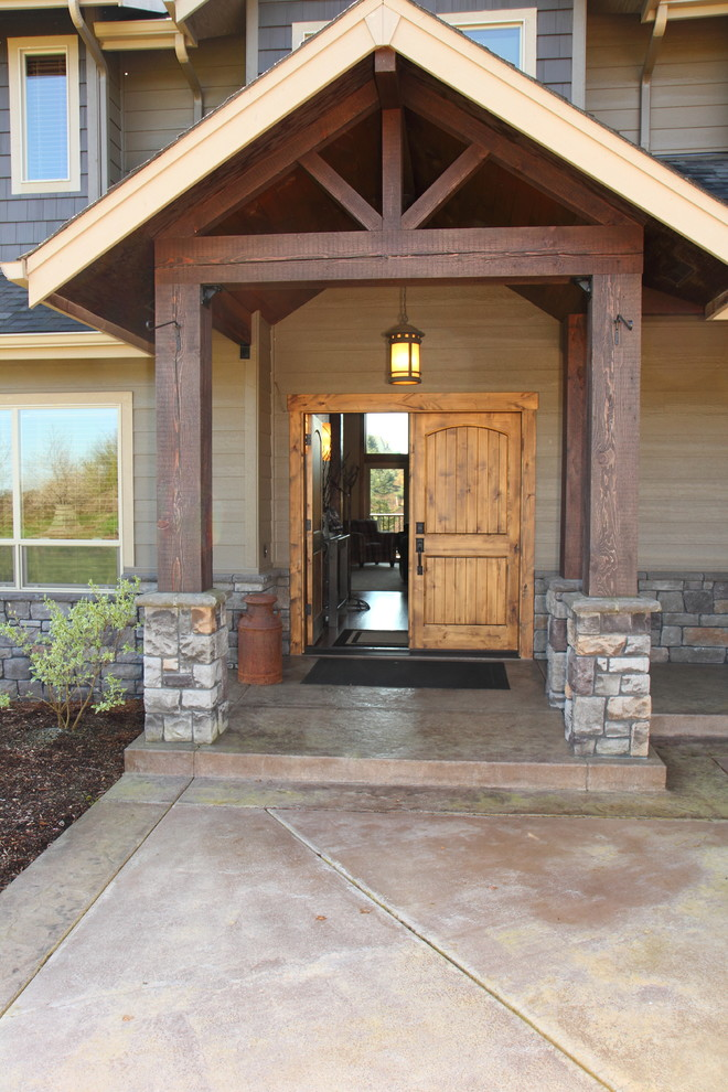 Inspiration for a large rustic stamped concrete front porch remodel in Portland with a roof extension
