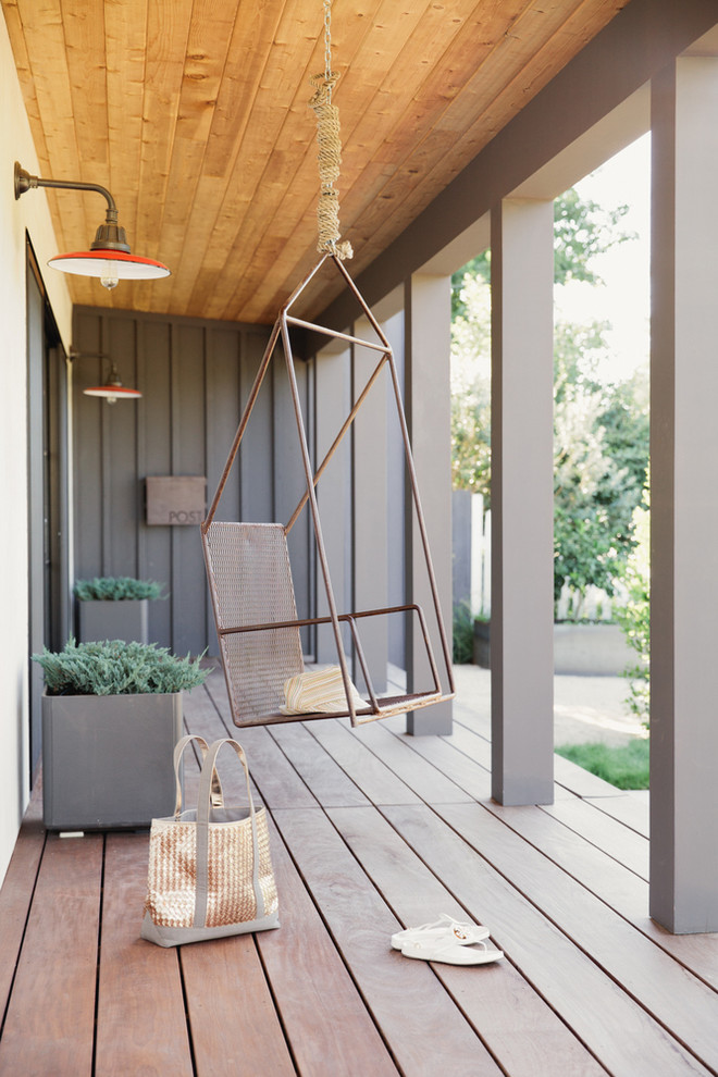 This is an example of a transitional porch design in San Francisco with decking and a roof extension.