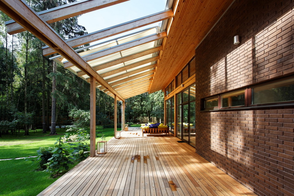 Trendy porch idea in Moscow with decking and a roof extension