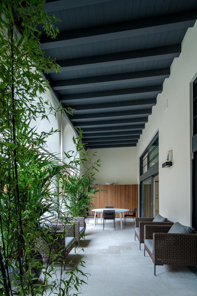 Idee per un grande portico design davanti casa con un giardino in vaso, pavimentazioni in pietra naturale e un tetto a sbalzo