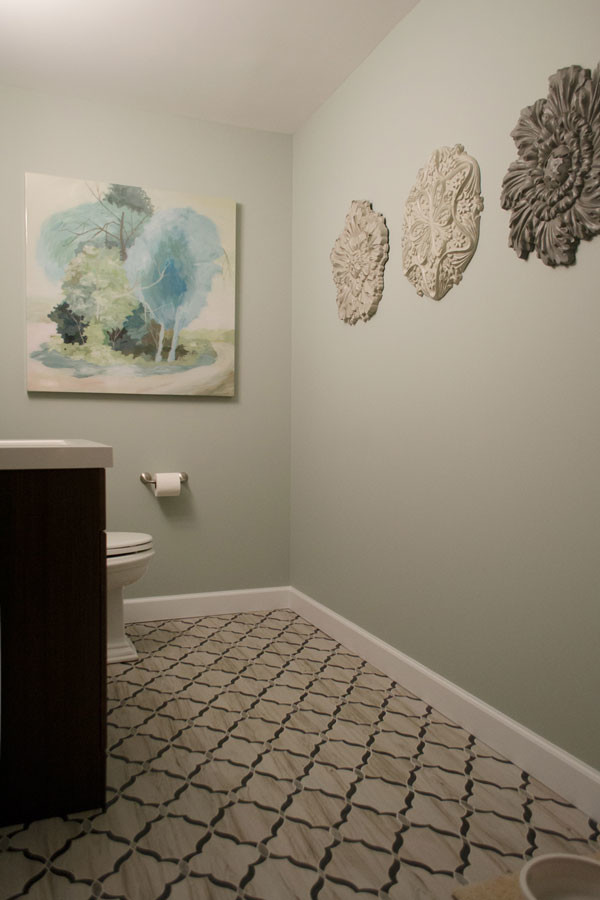 Small transitional ceramic tile and multicolored floor powder room photo in Louisville with flat-panel cabinets, brown cabinets, a one-piece toilet, blue walls, an undermount sink and quartzite countertops