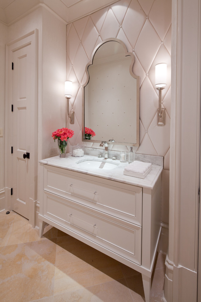 Inspiration for a small transitional beige tile limestone floor powder room remodel in Atlanta with an undermount sink, recessed-panel cabinets, white cabinets, marble countertops and white walls