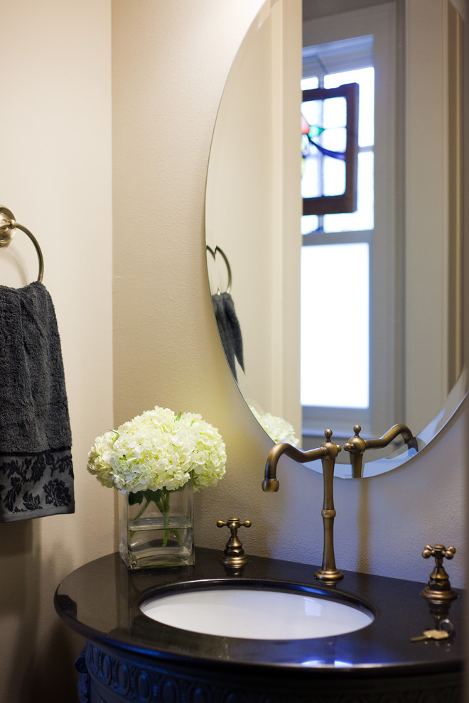 Inspiration for a timeless powder room remodel in Austin with solid surface countertops and black countertops