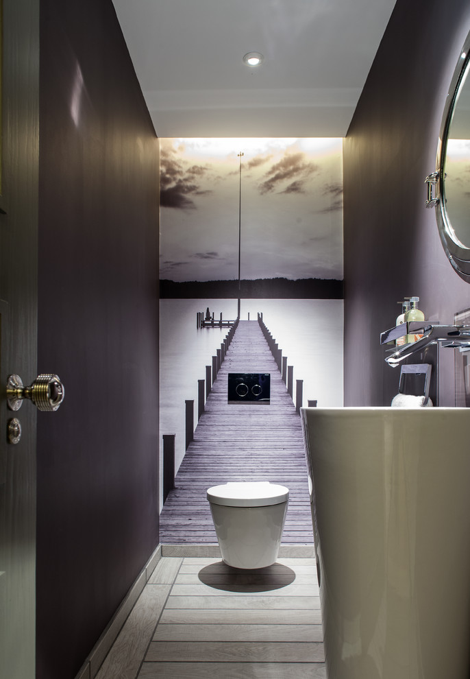 Example of a mid-sized trendy powder room design in London with a pedestal sink, a wall-mount toilet and purple walls