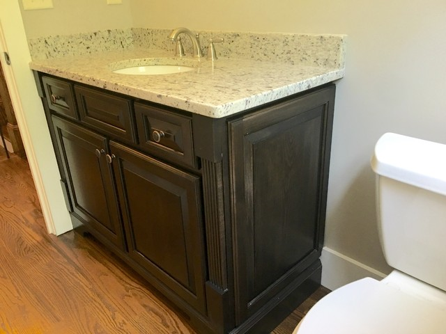 Inspiration for a mid-sized transitional medium tone wood floor powder room remodel in Atlanta with raised-panel cabinets, dark wood cabinets and an undermount sink