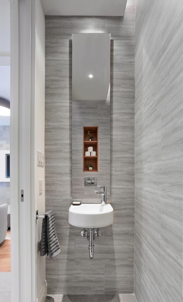Foto di un piccolo bagno di servizio design con piastrelle grigie, lavabo sospeso, pavimento grigio e pareti bianche