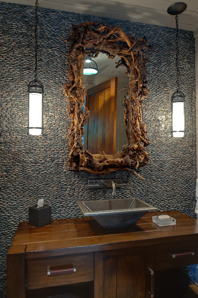 Example of a mountain style pebble tile powder room design in Atlanta with a vessel sink, wood countertops and brown countertops