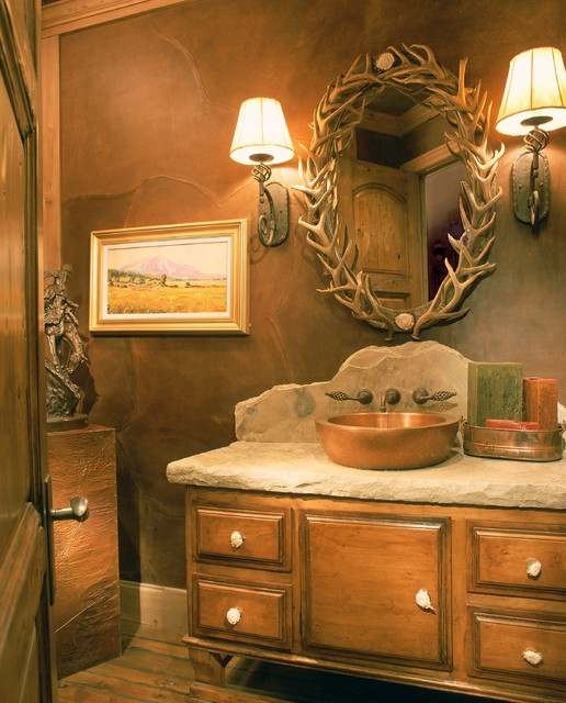 Example of a mid-sized mountain style dark wood floor powder room design in Denver with a vessel sink, medium tone wood cabinets, raised-panel cabinets, brown walls and beige countertops
