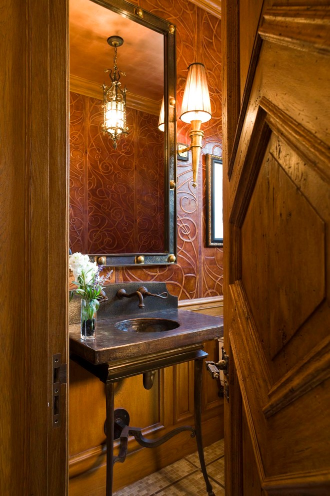 Small tuscan beige tile mosaic tile floor powder room photo in Denver with a two-piece toilet, brown walls, copper countertops and a console sink