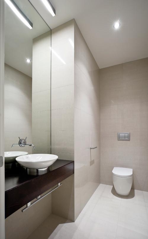 Mirror bathroom backsplash with floating faucets for Modern powder room design