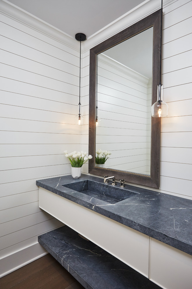 Inspiration for a transitional dark wood floor and brown floor powder room remodel in Other with flat-panel cabinets, white cabinets, white walls, an integrated sink and gray countertops