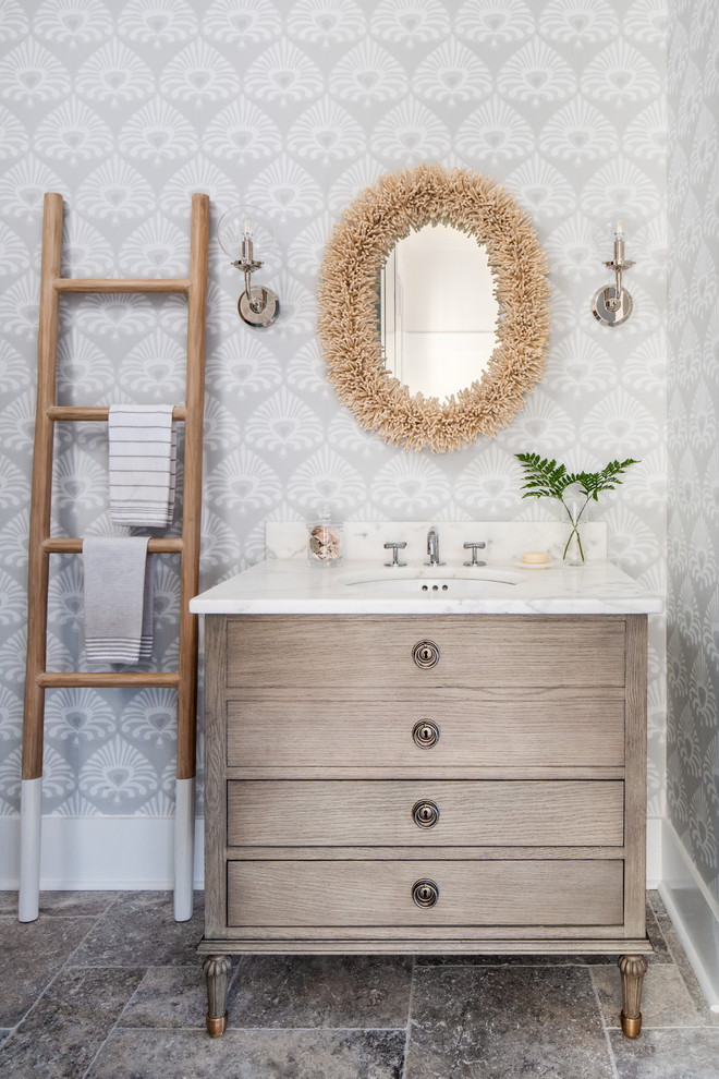 Powder room - coastal travertine floor powder room idea in Other with light wood cabinets, an undermount sink, marble countertops, white countertops, furniture-like cabinets and multicolored walls