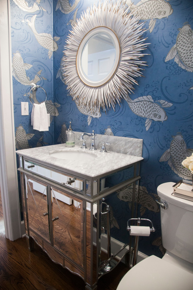 Example of a small ornate dark wood floor powder room design in New Orleans with an undermount sink, a two-piece toilet, furniture-like cabinets and white countertops