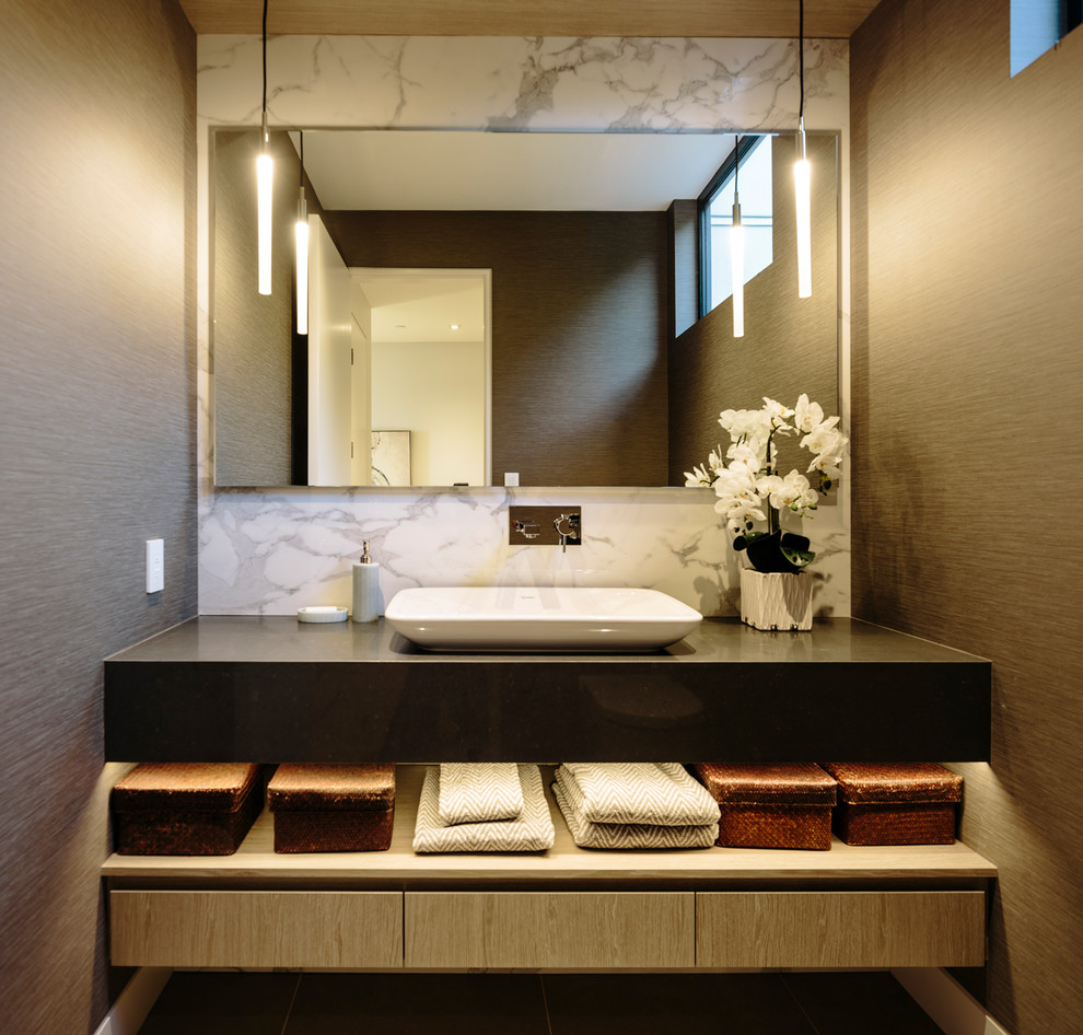 Large trendy brown tile and porcelain tile powder room photo in Vancouver with flat-panel cabinets, medium tone wood cabinets, a vessel sink, quartz countertops and gray countertops