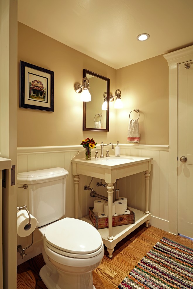 Inspiration for a small timeless medium tone wood floor powder room remodel in Los Angeles with a two-piece toilet, beige walls, an undermount sink, quartz countertops, open cabinets and white cabinets