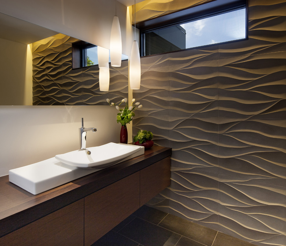 Powder room - contemporary gray tile powder room idea in Denver with a vessel sink, flat-panel cabinets, dark wood cabinets, wood countertops and brown countertops