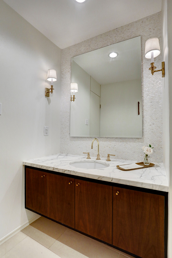 Powder room - mid-sized 1960s white tile and mosaic tile porcelain tile and beige floor powder room idea in Houston with flat-panel cabinets, dark wood cabinets, a one-piece toilet, white walls, an undermount sink, marble countertops and white countertops