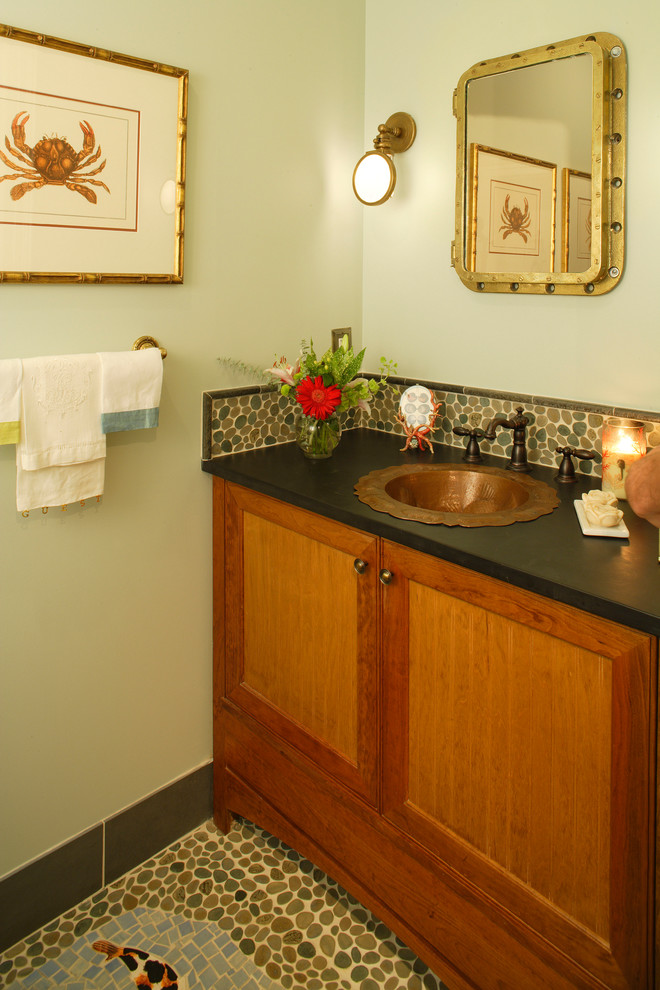 Example of a small beach style pebble tile powder room design in Philadelphia with a drop-in sink, recessed-panel cabinets, medium tone wood cabinets, green walls and black countertops