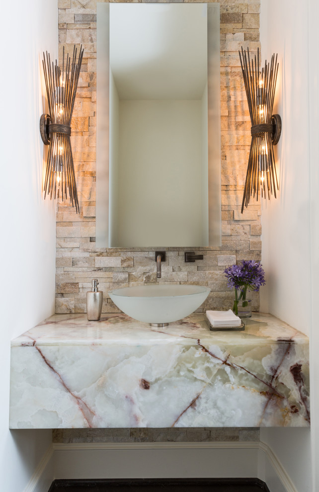 Example of a trendy beige tile and stone tile dark wood floor powder room design in Houston with white walls, a vessel sink, marble countertops and white countertops