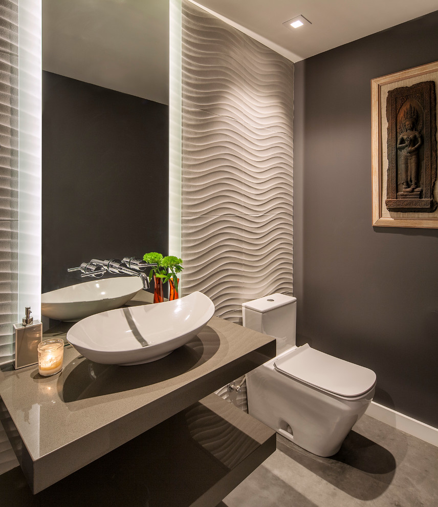 Example of a trendy concrete floor and gray floor powder room design in Santa Barbara with open cabinets, a one-piece toilet, gray walls, a vessel sink, solid surface countertops and gray countertops