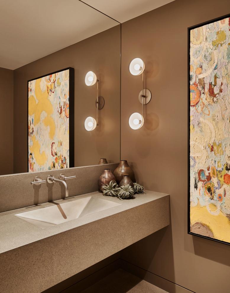 Imagen de aseo contemporáneo con paredes marrones, lavabo integrado, encimera de cemento y encimeras grises
