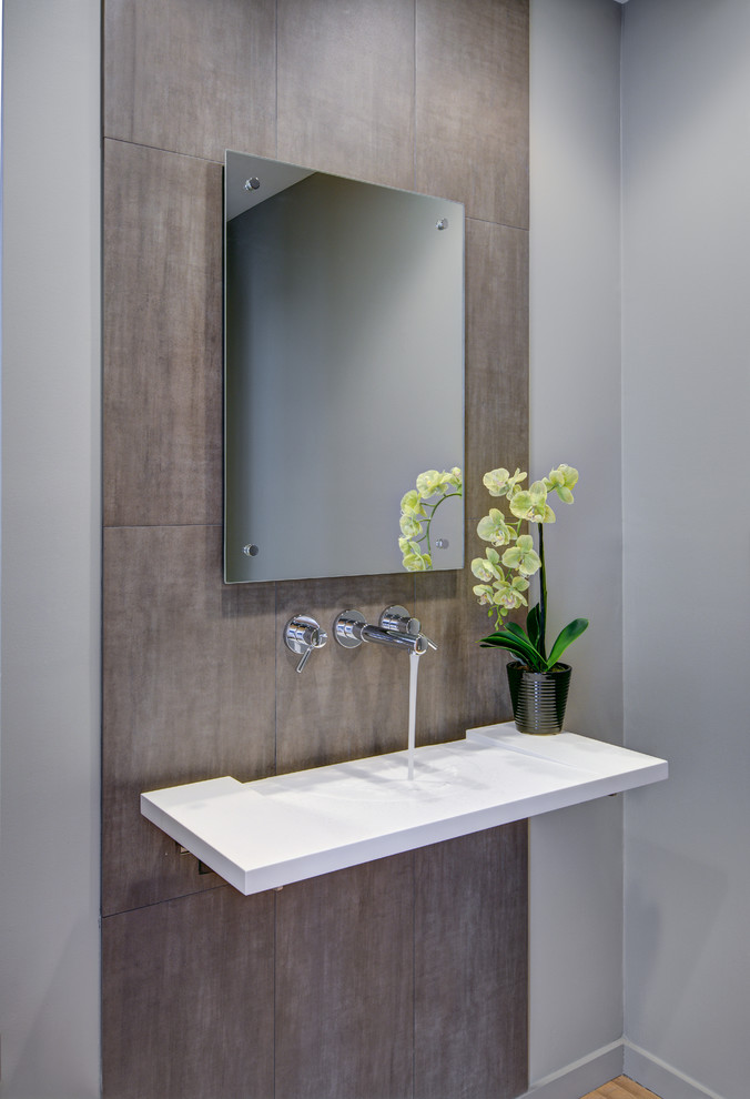 Powder room - small contemporary brown tile and porcelain tile powder room idea in Detroit with a wall-mount sink, gray walls and solid surface countertops