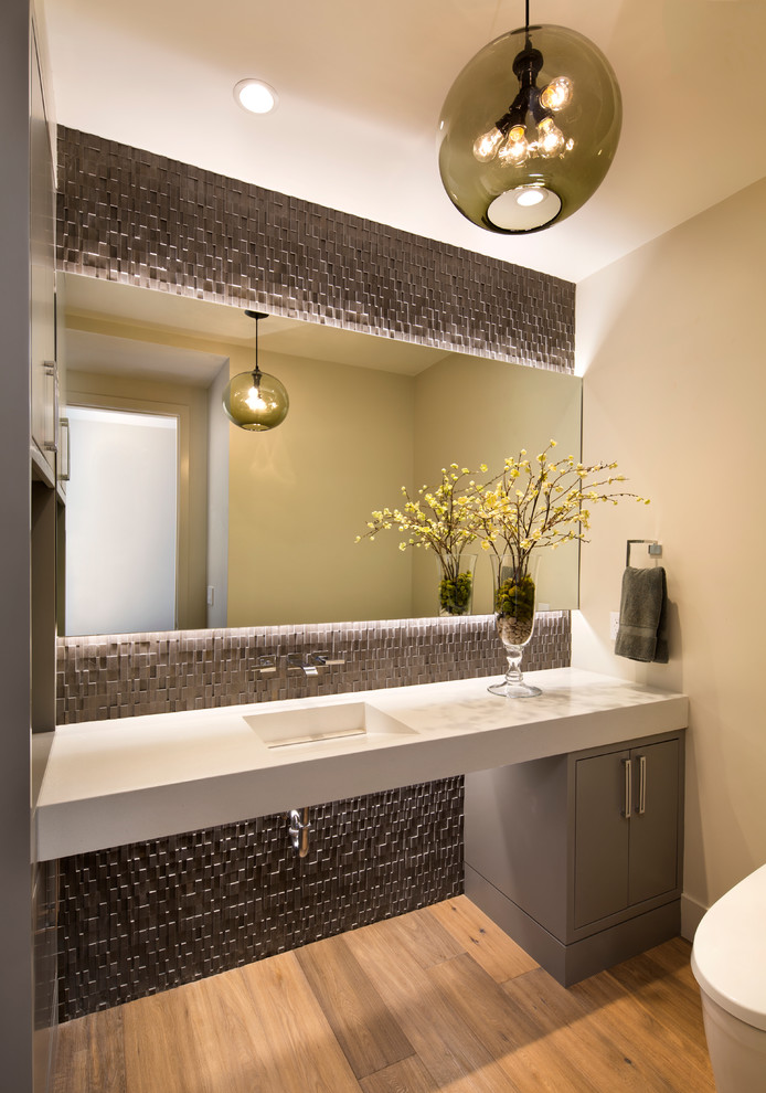 Powder room - contemporary light wood floor powder room idea in San Francisco with flat-panel cabinets, gray cabinets, beige walls and an integrated sink