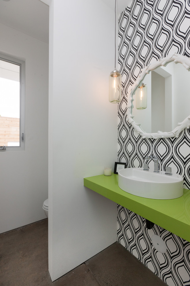 Inspiration for a contemporary concrete floor and brown floor powder room remodel in Orange County with a vessel sink, white walls and green countertops