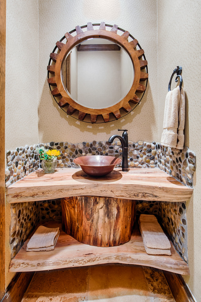 Inspiration for a rustic powder room remodel in Other with a vessel sink