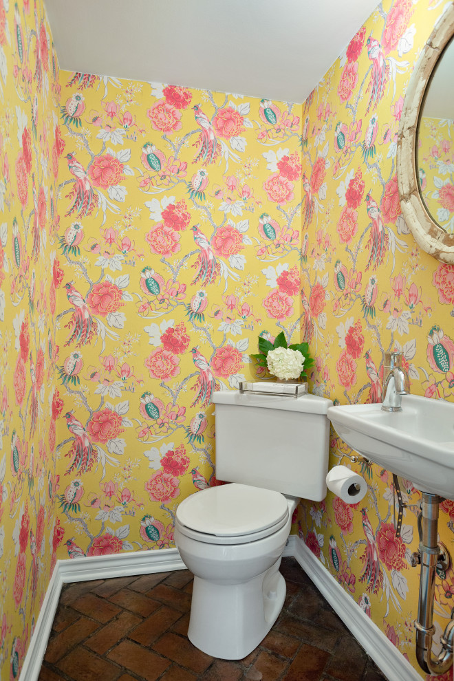 Example of a small brick floor and red floor powder room design in Dallas with a two-piece toilet, yellow walls and a wall-mount sink