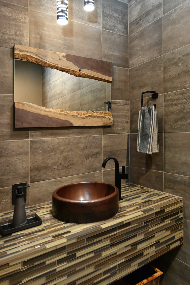 Inspiration for a mid-sized contemporary powder room in Tampa with a vessel sink, tile benchtops, gray tile and brown tile.