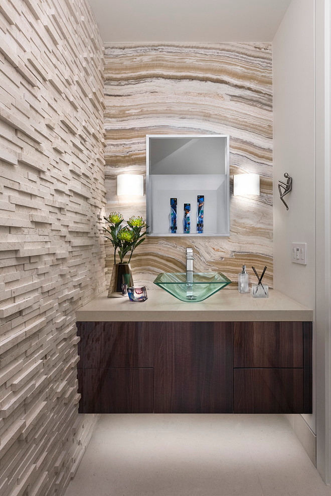 Powder room - small contemporary beige tile gray floor powder room idea in Los Angeles with flat-panel cabinets, dark wood cabinets, a vessel sink, beige countertops and beige walls