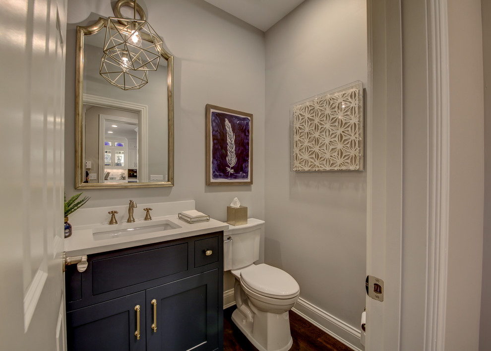 Inspiration for a mid-sized transitional dark wood floor and brown floor powder room remodel in Dallas with shaker cabinets, black cabinets, a two-piece toilet, gray walls, an undermount sink, quartz countertops and white countertops
