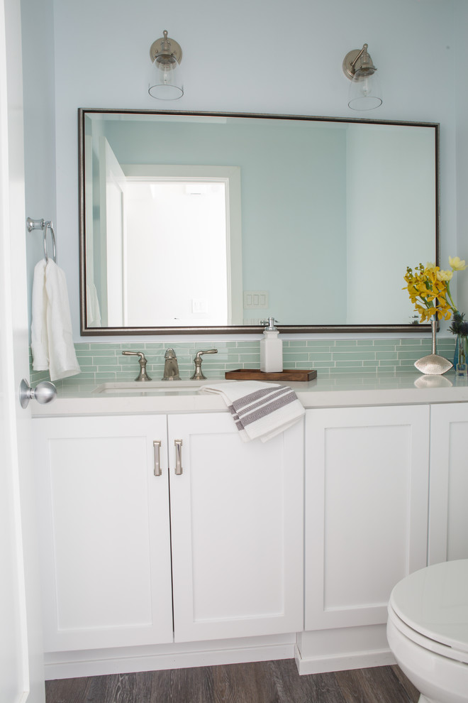 Inspiration for a small coastal green tile and glass tile vinyl floor powder room remodel in Los Angeles with a one-piece toilet, an undermount sink, quartz countertops and recessed-panel cabinets