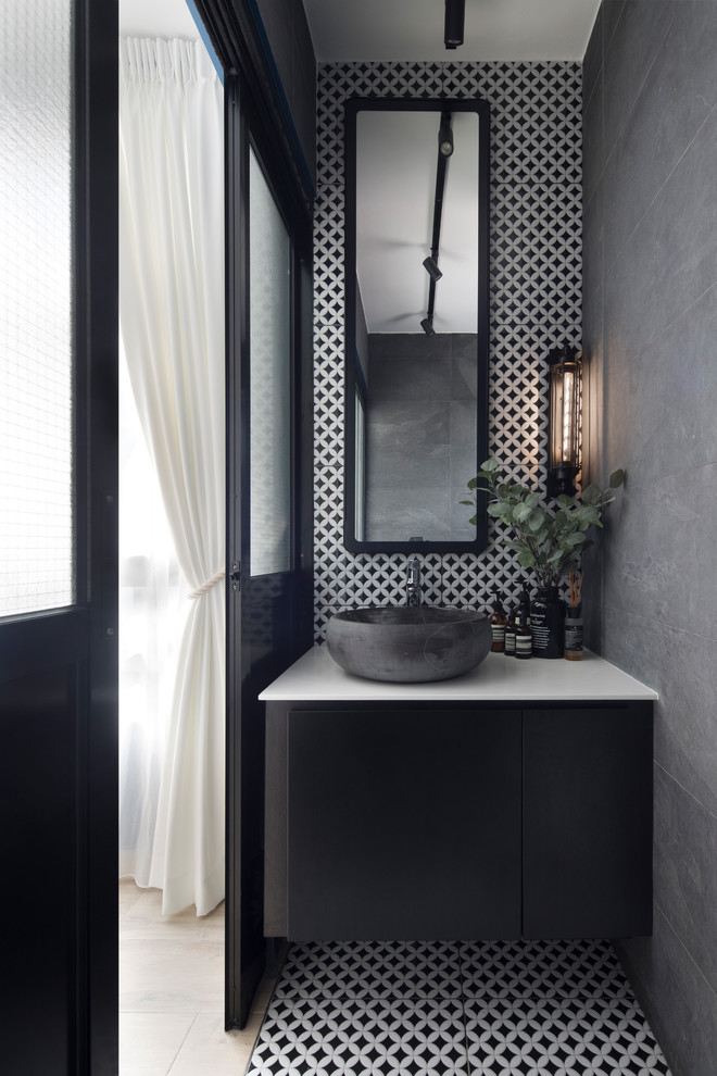 Inspiration for a small scandinavian black and white tile multicolored floor powder room remodel in Singapore with flat-panel cabinets, black cabinets, gray walls, a vessel sink and white countertops