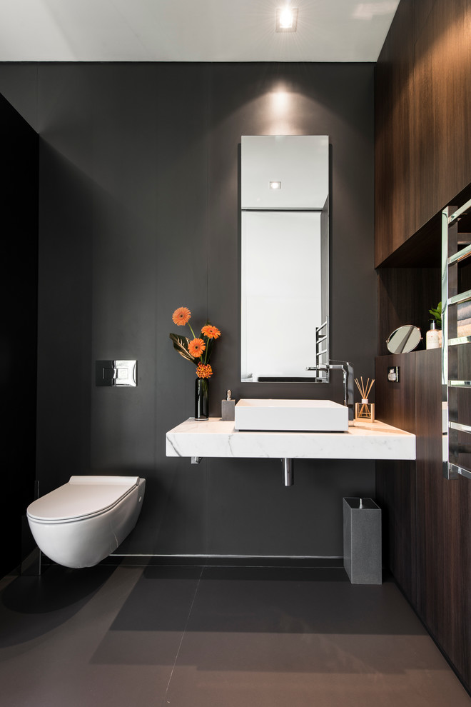 Mid-sized trendy ceramic tile powder room photo in Perth with a vessel sink, dark wood cabinets, marble countertops, a wall-mount toilet and black walls